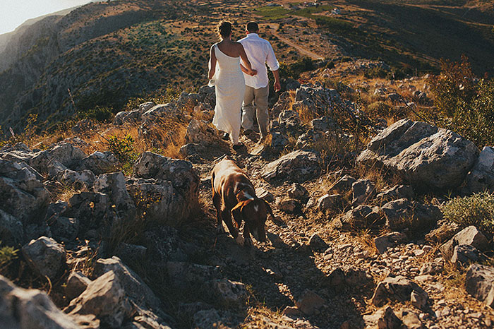 bride and groom walking down cliff