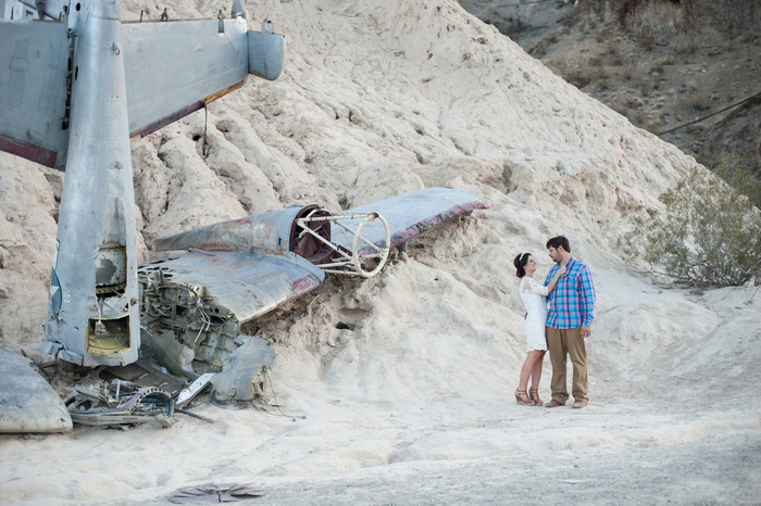 bride and groom portrait in the desert with plane wrackage