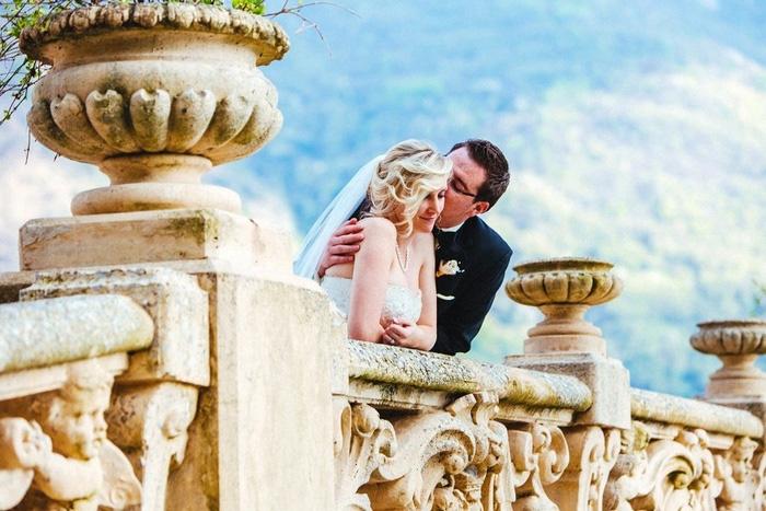 Bride and groom on villa balcony