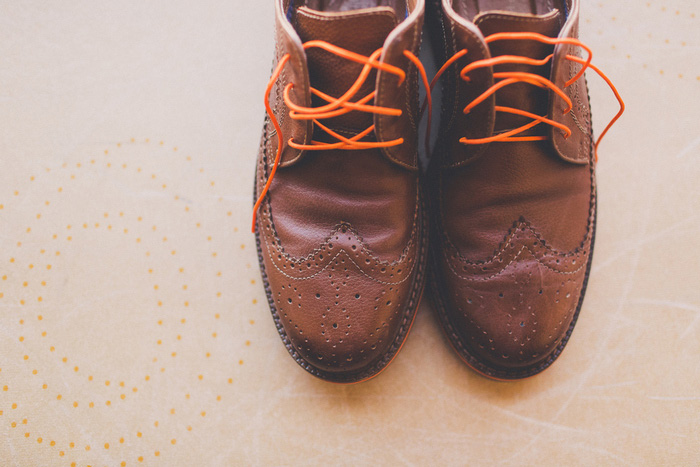groom's wedding shoes with orange laces