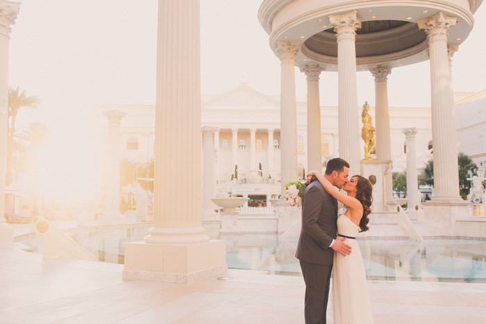 bride and groom kissing by the pool