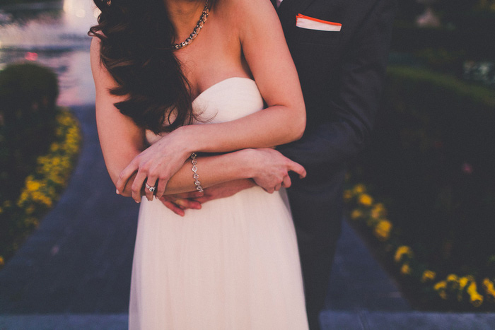 groom's arms wrapped around bride