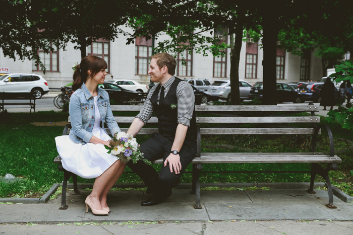 bride and groom sitting on New York City park bench