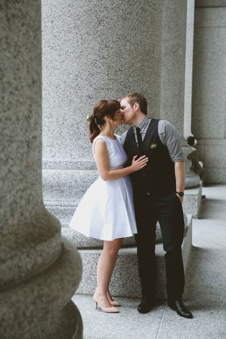 bride and groom kissing outside city hall