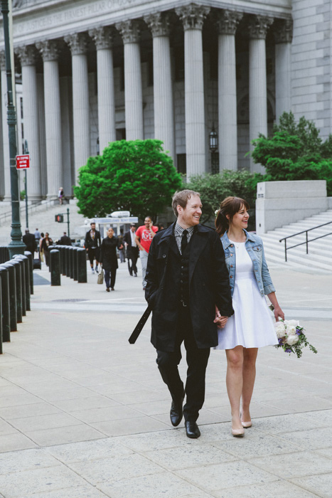 bride and groom strolling outside city hall