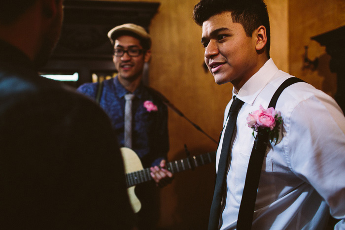 groom in suspenders and pink boutonniere