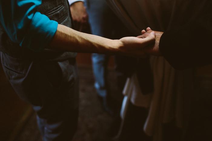 groomsmen holding hands in prayer