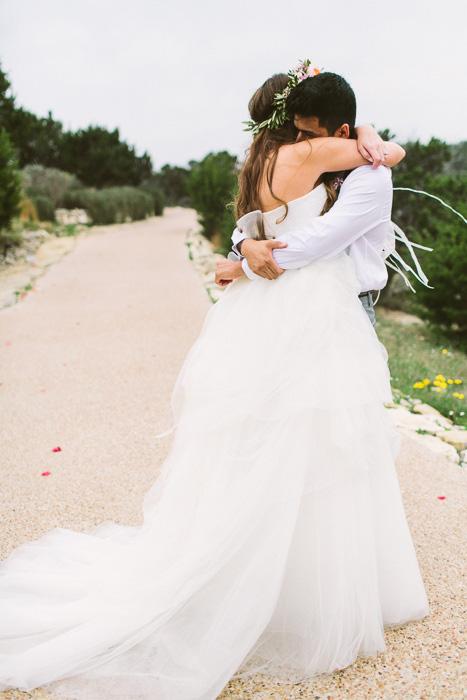 bride and groom hugging on dirt road