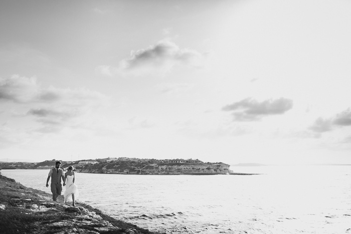 bride and groom walking by the ocean