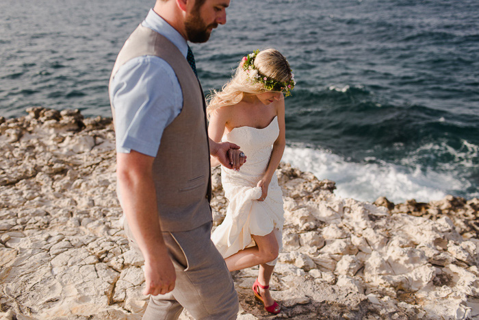 bride holding up her dress walking with groom by the ocean