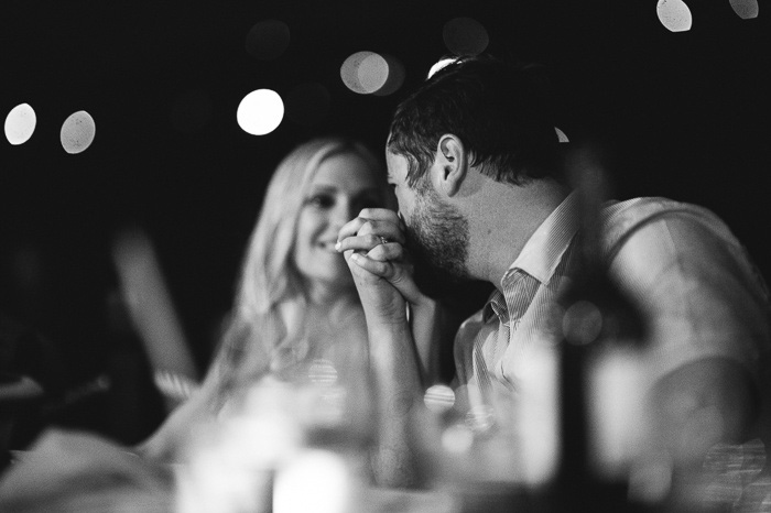 groom kissing bride's hand at reception