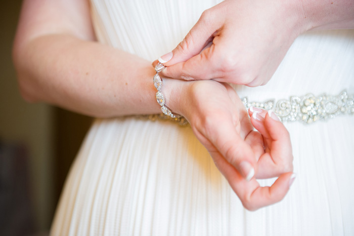 bride putting on bracelet