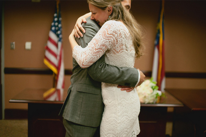 bride and groom hugging in courthouse