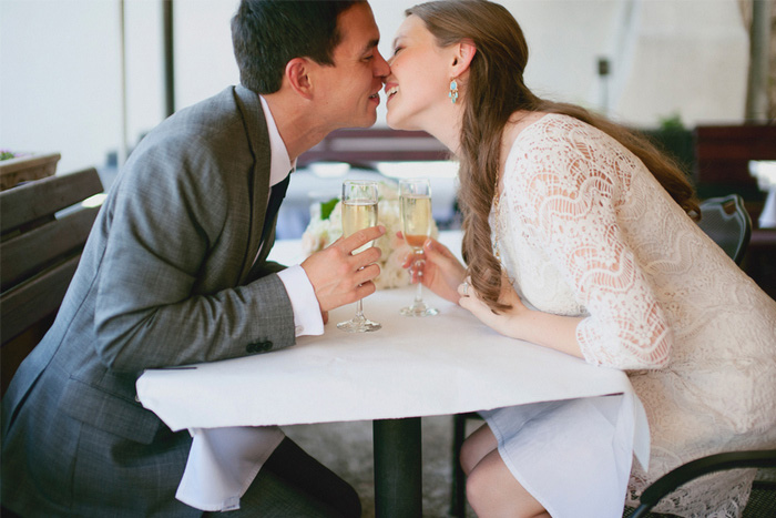 bride and groom kissing over champagne