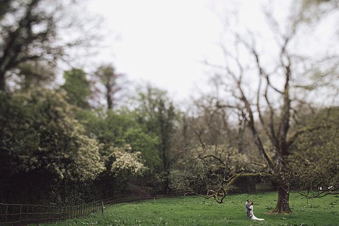 bride and groom walking through irish countryside