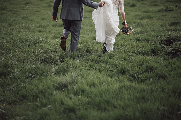 bride and groom walking through irish countryside