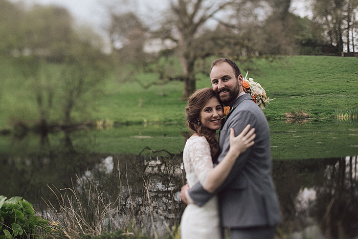 bride and groom embracing by pond