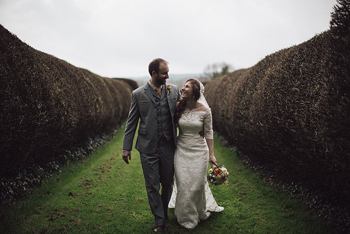 bride and groom strolling on country house grounds