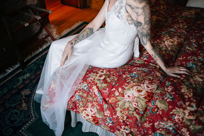 tattooed bride sitting on bed