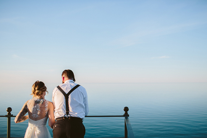 bride and groom looing over lighthouse railing