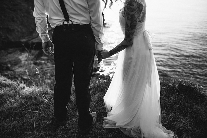 bride and groom walking by lake