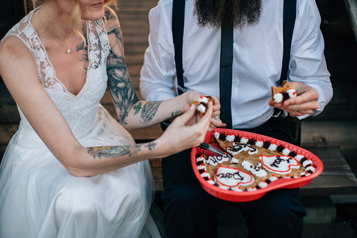 bride and groom sharing heart shaped cookie cake