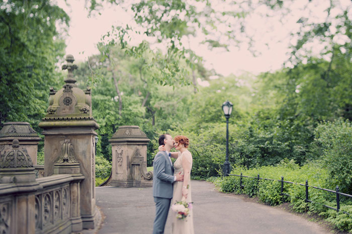 groom kissing bride's forehead in central park