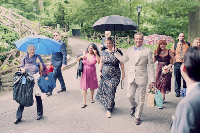 wedding guests walking under umbrellas in Central Park