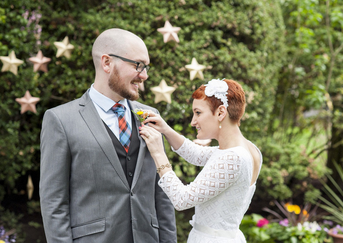 bride pinning boutonniere on groom