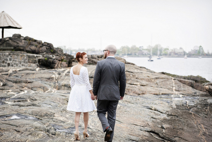 bride and groom walking by the water