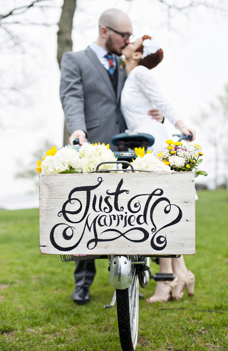 couple kissing behind just married sign