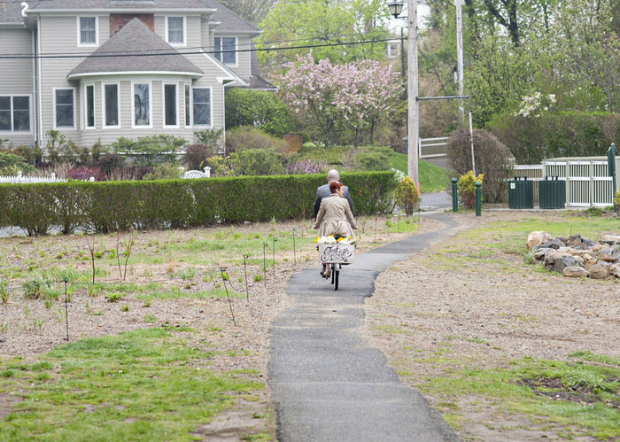 bride and groom riding away on tandem bike