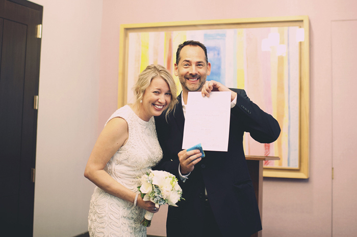 bride and groom with marriage certificate