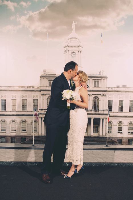 bride and groom kissing at city hall