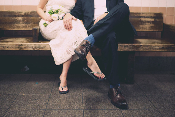 bride and groom sitting on subway bench
