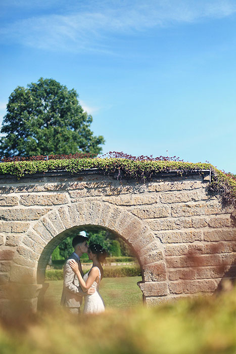 bride and groom under brick archway