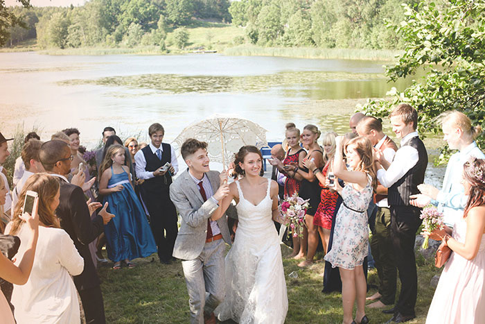 bride and groom walking through crowd of guests