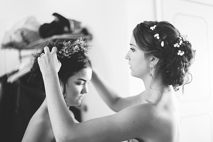 bride placing flower crown on bridesmaid