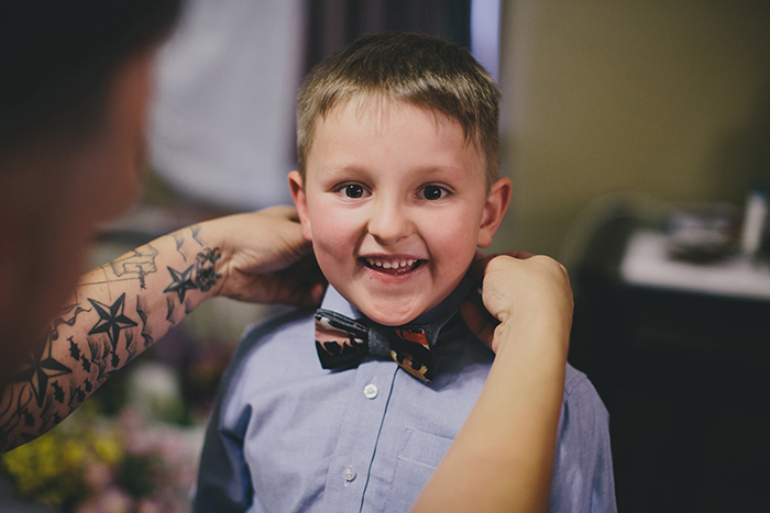 groom putting bow tie on his son