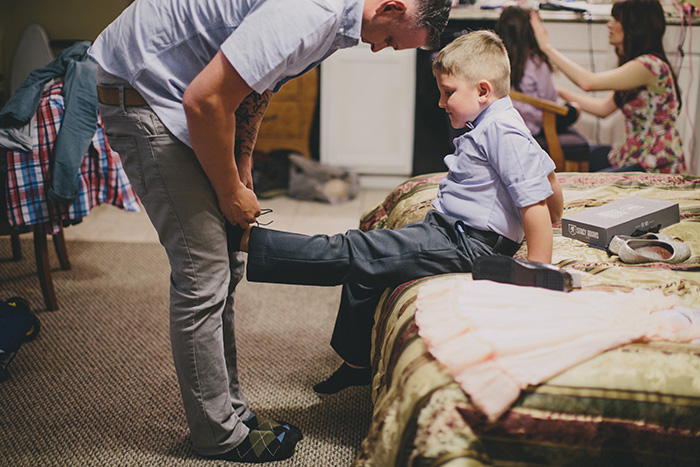 groom tying son's shoes