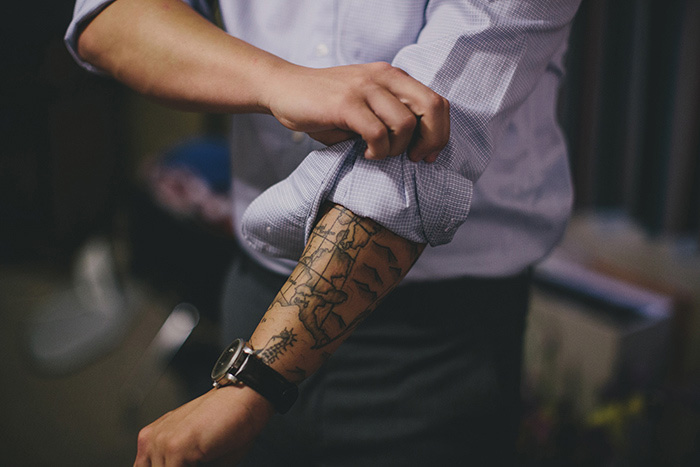 tattoed groom rolling up his sleeves