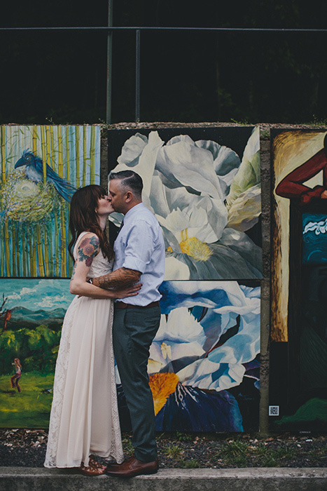 bride and groom kissing in front of mural