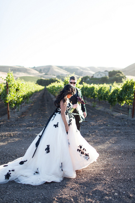 bride and groom walking next to grape vines