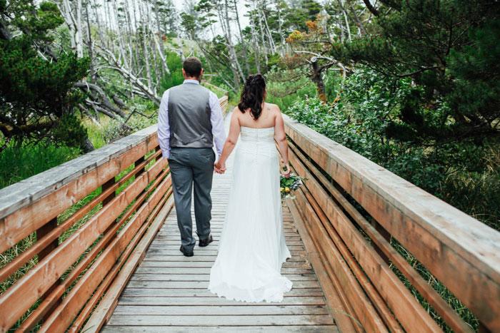 bride and groom walking across wooden bridge