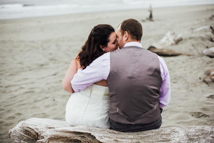 bride and groom sitting on driftwood log
