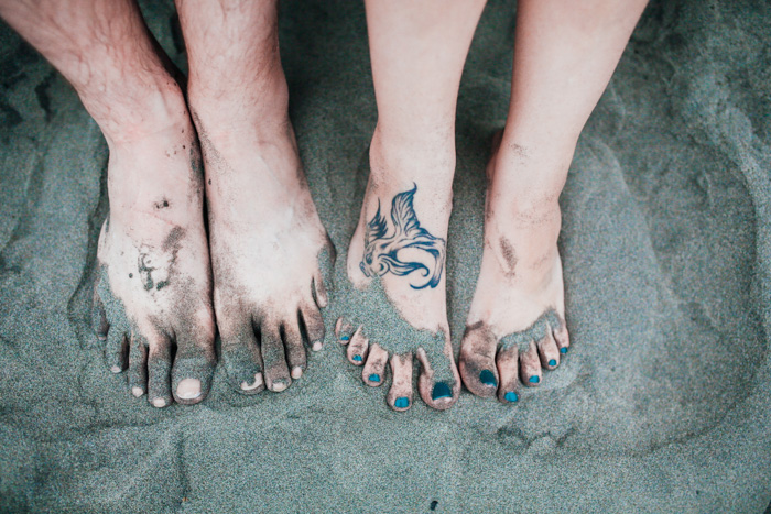 couple's feet in the sand