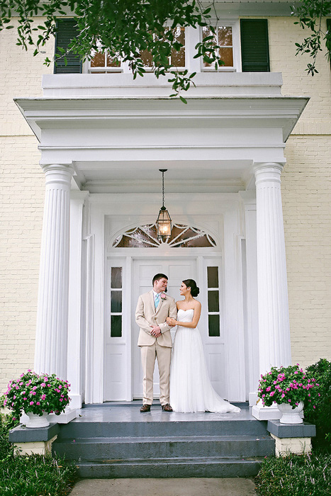 bride and groom on front step of estate
