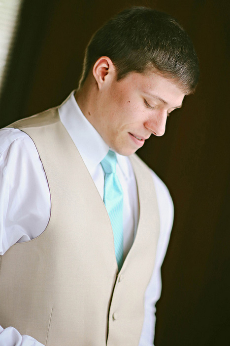 groom in beige vest and turquoise tie