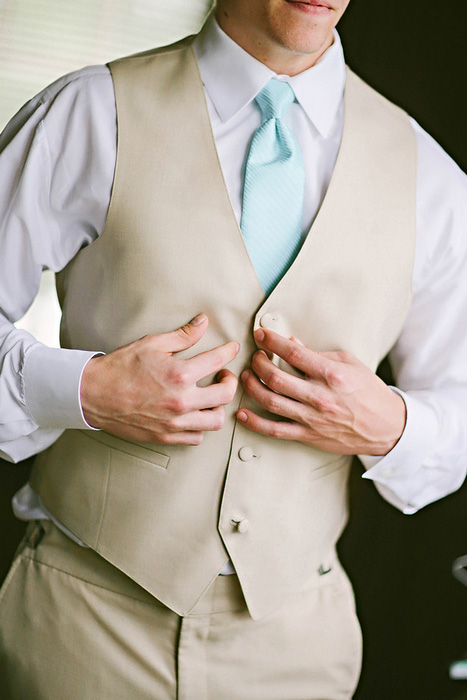 groom buttoning vest