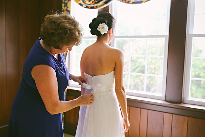 mother helping bride with her dress